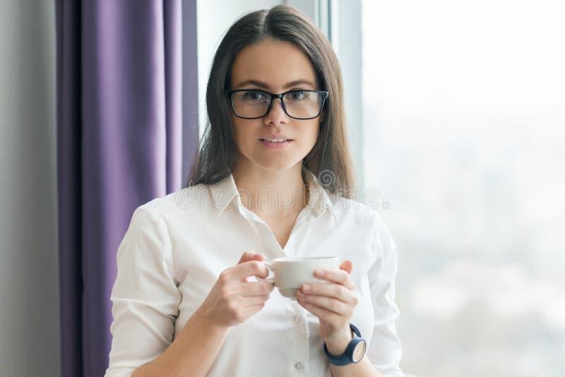 Retrato da mulher de negócios nova em vidros vestindo da camisa branca com xícara de café, levantando a mulher de sorriso que olh imagens de stock royalty free