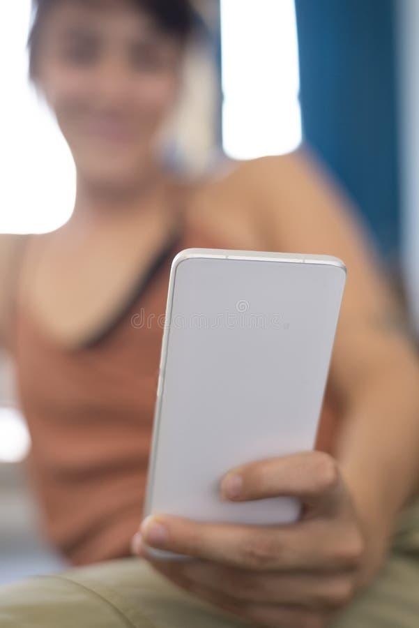 Retrato da mulher de negócios nova feliz que usa o telefone celular no offi fotografia de stock royalty free