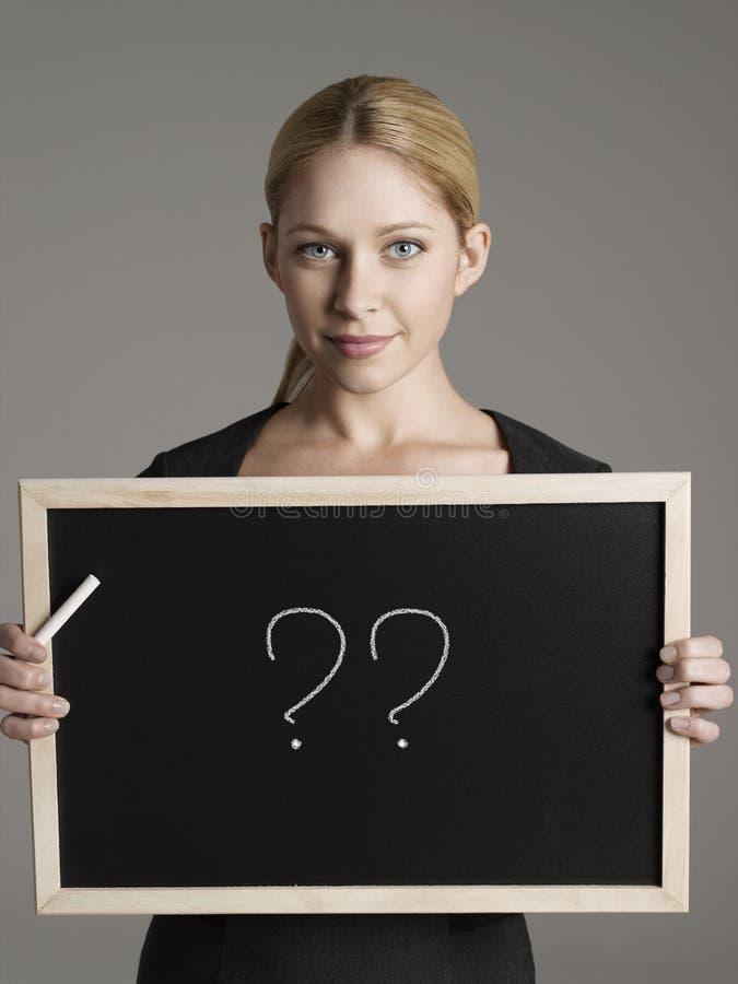 Retrato da mulher de negócios nova que guarda o quadro-negro com pontos de interrogação imagens de stock royalty free