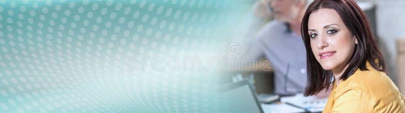 Retrato da mulher de negócios nova que senta-se na mesa, bandeira panorâmico fotografia de stock