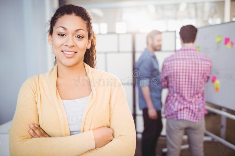 Retrato da mulher de negócios nova segura que está no escritório criativo imagem de stock