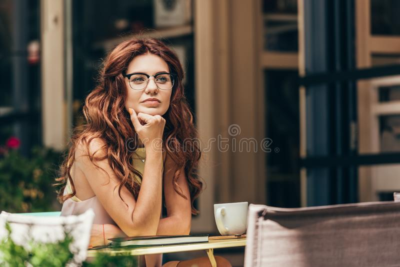 retrato da mulher de negócios pensativa nos monóculos na tabela com xícara de café e caderno fotos de stock
