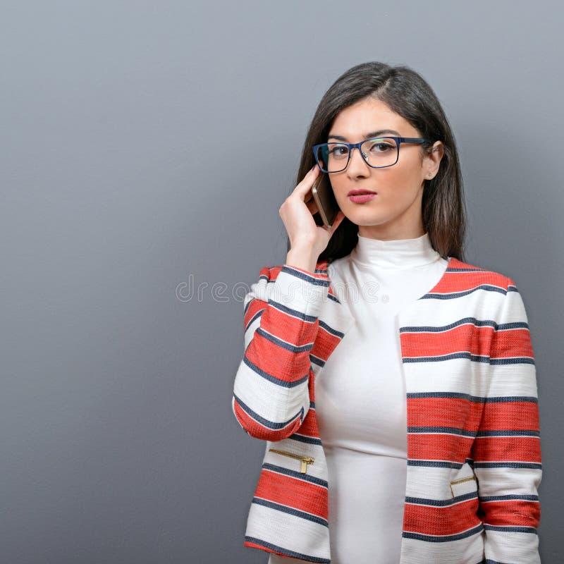 Retrato da mulher de negócios que usa o telefone celular contra o fundo cinzento fotografia de stock royalty free