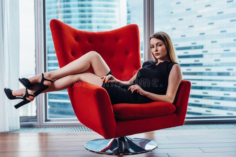 Retrato da mulher de negócios 'sexy' que relaxa na poltrona à moda no escritório imagem de stock
