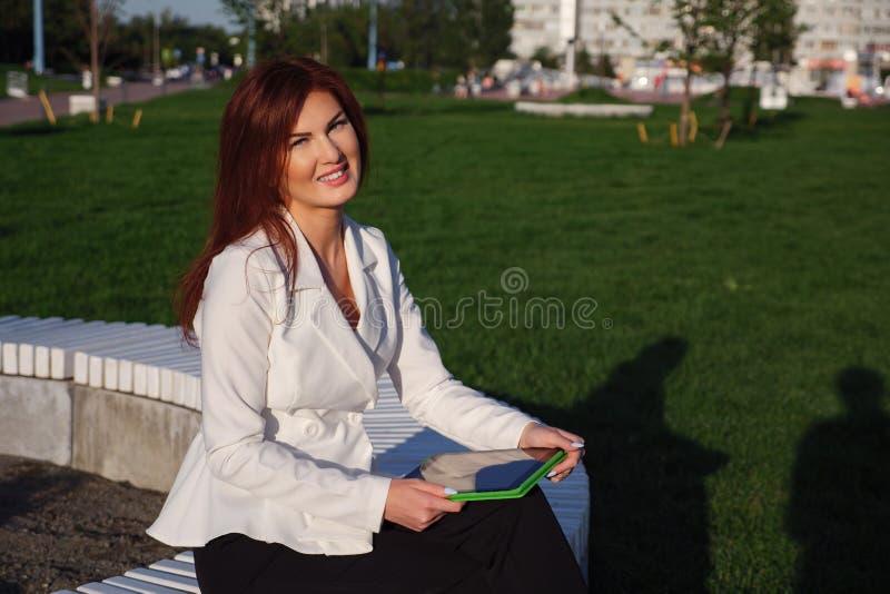 Retrato da mulher de negócios de sorriso no terno com a tabuleta exterior foto de stock royalty free