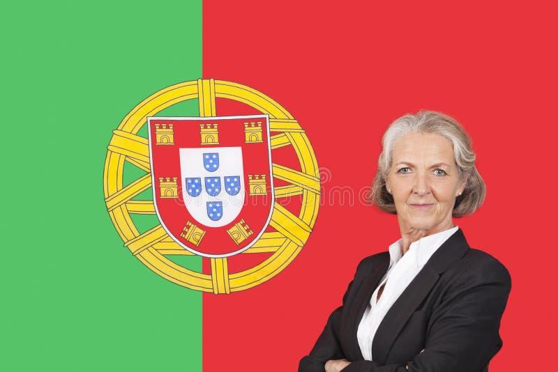 Retrato da mulher de negócios superior com orgulho sobre a bandeira portuguesa foto de stock