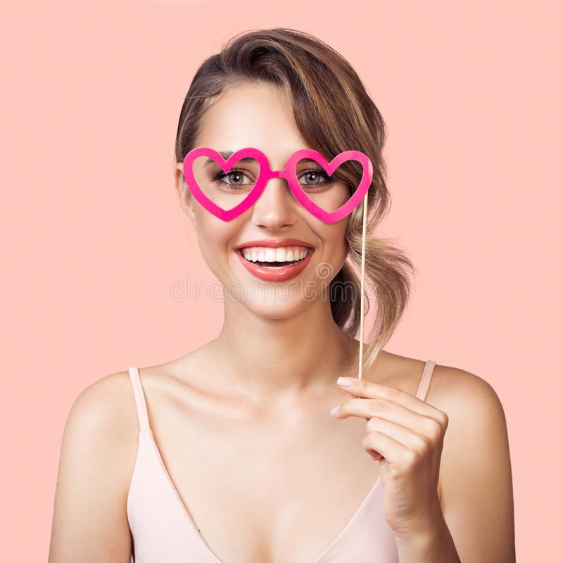 Retrato da mulher de sorriso alegre que guarda o coração de papel dos vidros do partido à disposição imagens de stock