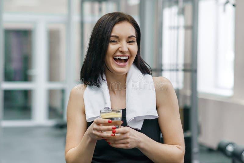 Retrato da mulher de sorriso da aptidão com vidro da água com limão, mulher no sportswear após a água potável das classes da apti foto de stock