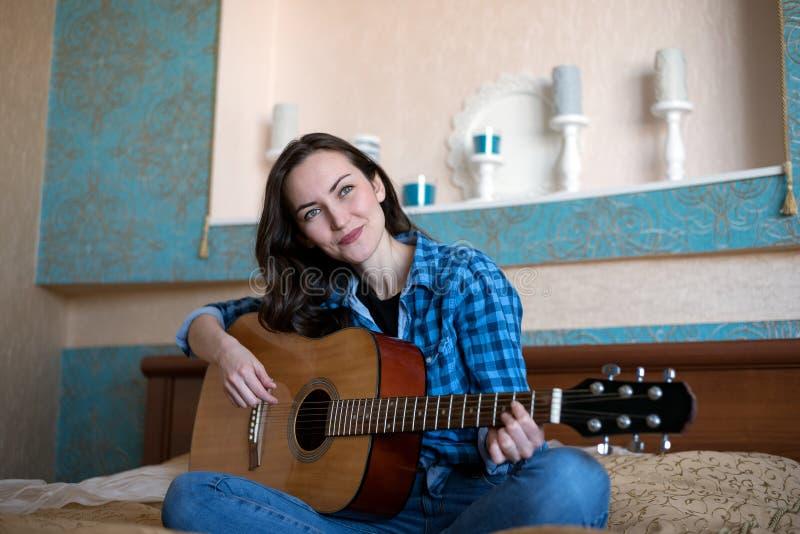 Retrato da mulher de sorriso atrativa nova com guitarra acústica fotografia de stock