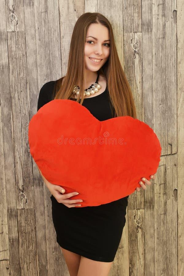Retrato da mulher de sorriso bonita com coração vermelho fotografia de stock