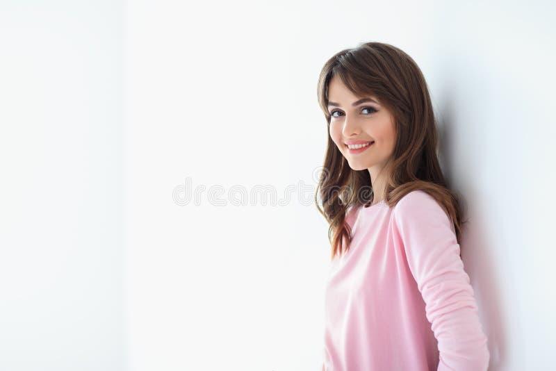 Retrato da mulher de sorriso bonita com os braços cruzados em b branco foto de stock royalty free