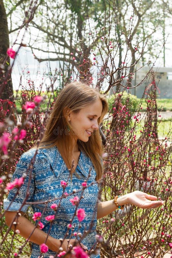 Retrato da mulher de sorriso bonita nova com cabelo louro em um jardim com árvores de florescência foto de stock royalty free