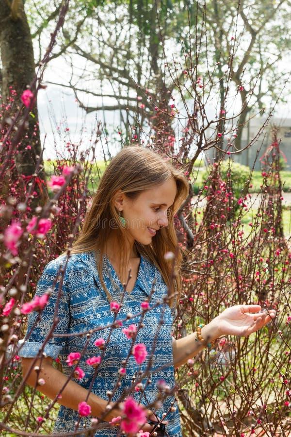 Retrato da mulher de sorriso bonita nova com cabelo louro em um jardim com árvores de florescência imagens de stock