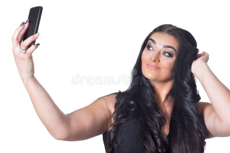 Retrato da mulher de sorriso bonita que toma o selfie com o smartphone isolado no fundo branco foto de stock