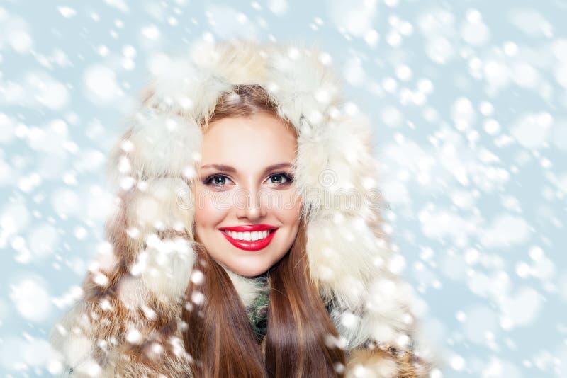 Retrato da mulher de sorriso bonito na capa da pele no fundo da neve do inverno imagem de stock royalty free
