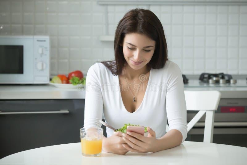 Retrato da mulher de sorriso com o smartphone que tem o almoço saudável fotos de stock royalty free