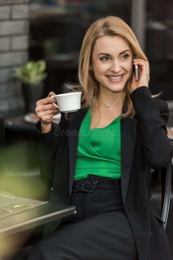 retrato da mulher de sorriso com xícara de café que fala no smartphone imagem de stock