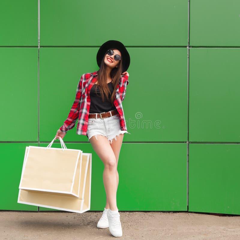 Retrato da mulher de sorriso da forma da beleza com os sacos de compras nos óculos de sol no fundo verde outdoor Copyspace imagens de stock royalty free
