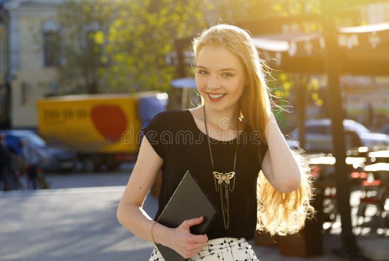Retrato da mulher de sorriso europeia com portátil que anda na rua da cidade imagem de stock