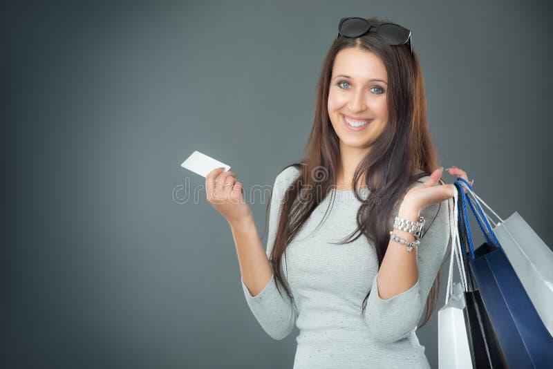 Retrato da mulher de sorriso feliz nova com o cartão e as sapatas de crédito dos sacos de compras fotos de stock royalty free