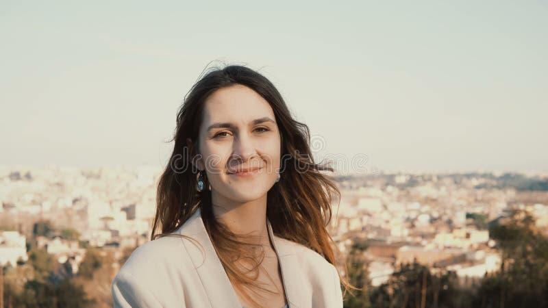 Retrato da mulher de sorriso feliz que está contra o panorama de Roma, Itália Câmera de vista fêmea, apreciando o dia imagem de stock