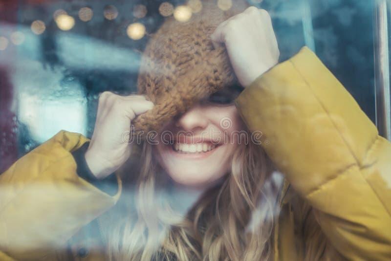 Retrato da mulher de sorriso feliz que puxa seu chap?u imagens de stock royalty free