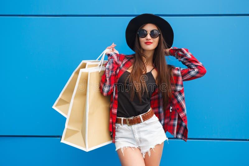 Retrato da mulher de sorriso da forma da beleza com os sacos de compras nos óculos de sol no fundo azul outdoor Copyspace imagens de stock