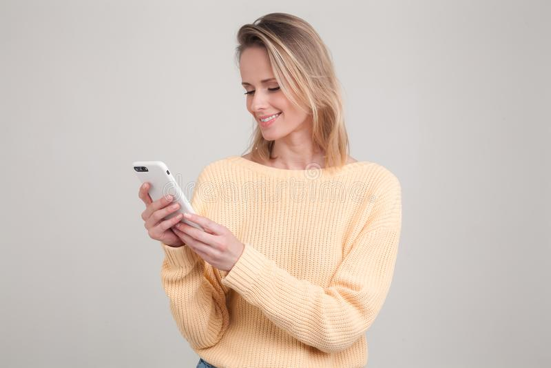 Retrato da mulher de sorriso loura nova que usa o telefone celular, mensagem, estando feliz conversar com seu noivo camiseta amar imagem de stock royalty free