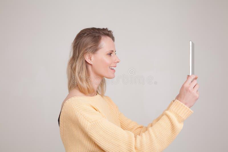 Retrato da mulher de sorriso loura nova que usa a tabuleta, mensagem, estando feliz conversar com seu noivo olhando a tela da pil imagens de stock