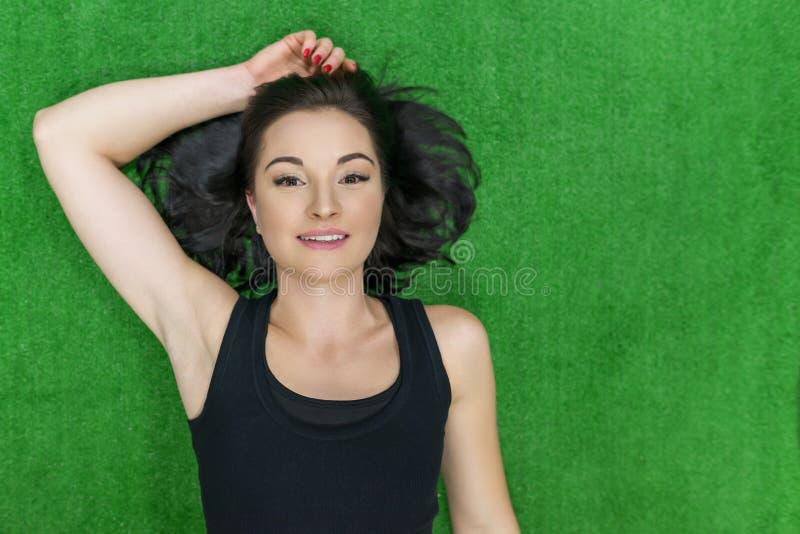 Retrato da mulher de sorriso nova da aptidão que coloca no assoalho no gym Vista superior, mulher moreno na superfície verde, esp fotos de stock royalty free