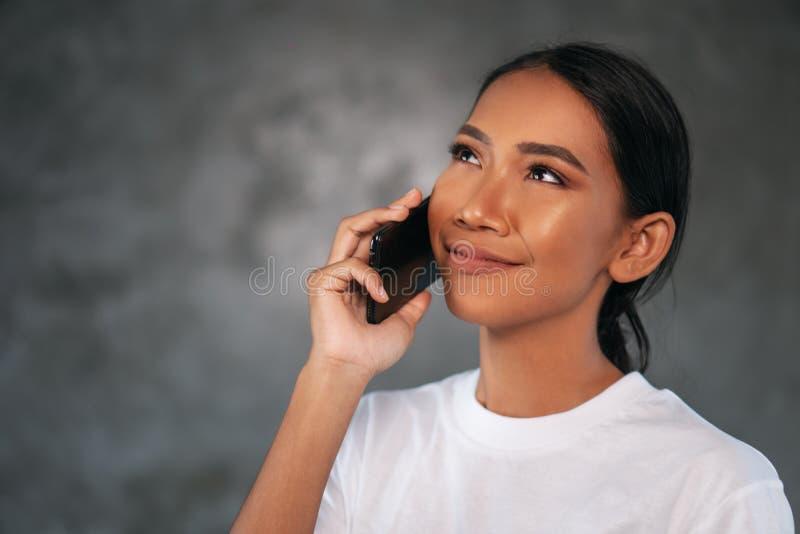 Retrato da mulher de sorriso nova bonita com telefone celular imagem de stock