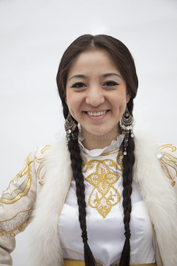 Retrato da mulher de sorriso nova com as tranças na roupa tradicional de Cazaquistão, tiro do estúdio fotos de stock