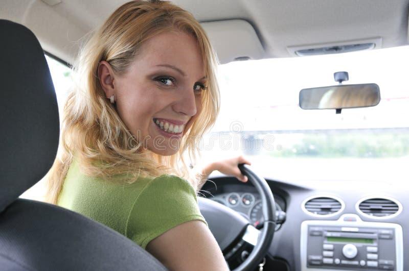 Retrato da mulher de sorriso nova dentro de um carro imagens de stock