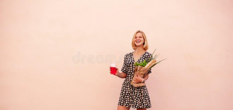 Retrato da mulher de sorriso nova do estudante com o saco da loja de ofício, com salada verde, cebola e pão Alimento saudável do  fotos de stock royalty free