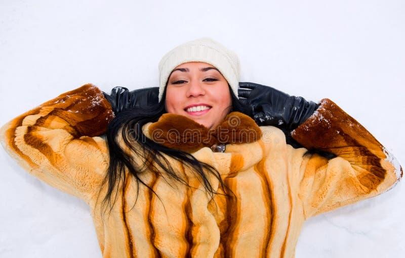 Retrato da mulher de sorriso nova na neve fotografia de stock royalty free