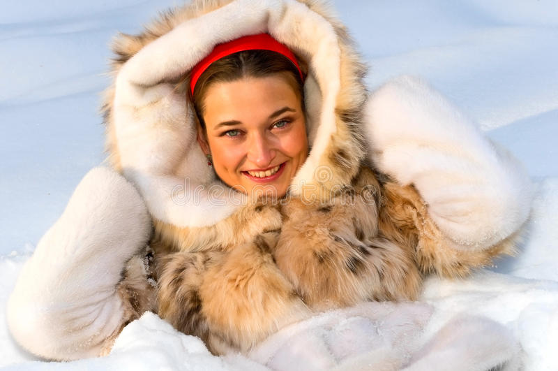 Retrato da mulher de sorriso nova na neve imagem de stock
