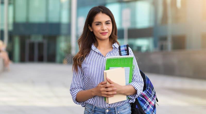 Retrato da mulher de sorriso nova que guarda livros, estudo, educação, conhecimento, conceito do objetivo imagem de stock