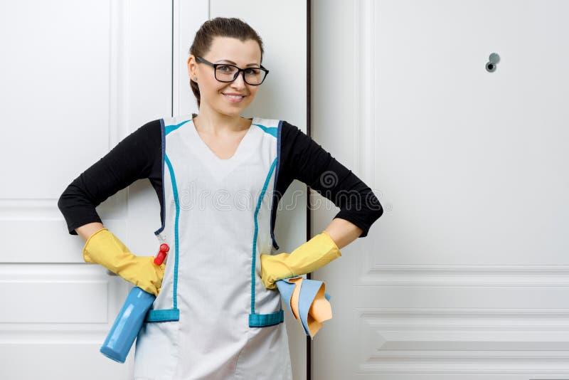 Retrato da mulher de sorriso positiva adulta nos vidros e no avental para luvas de borracha de limpeza com detergentes, fundo bra imagens de stock royalty free