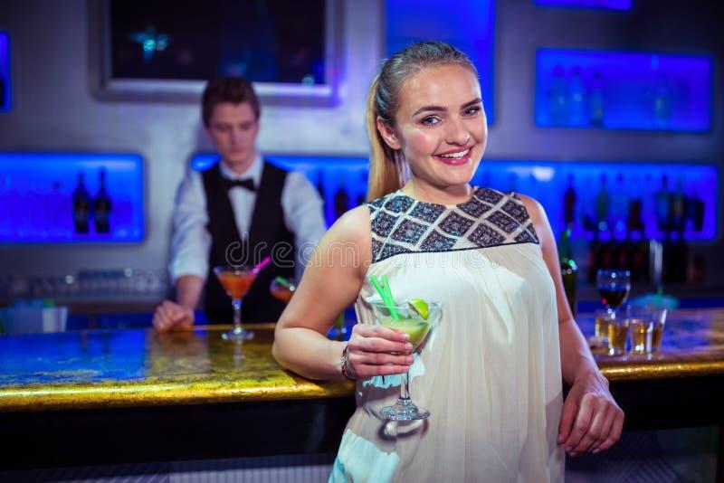 Retrato da mulher de sorriso que está contra o barman fotografia de stock
