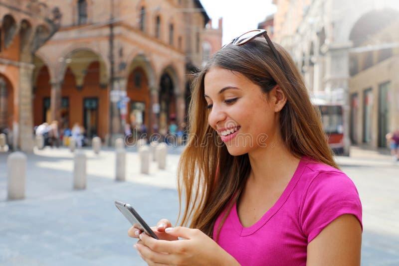 Retrato da mulher de sorriso que usa o telefone esperto na cidade medieval velha imagem de stock