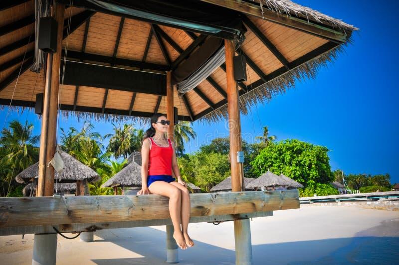 Retrato da mulher de vista asiática nova que senta-se na cabana na praia tropical bonita imagem de stock royalty free