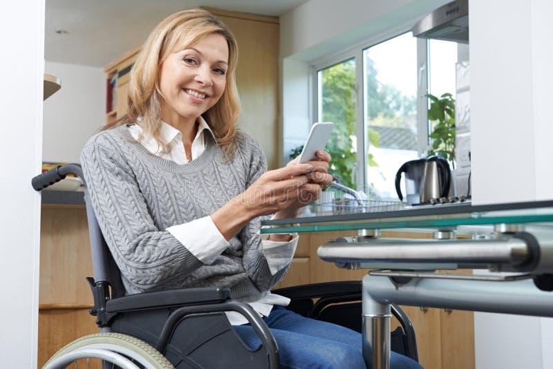 Retrato da mulher deficiente na cadeira de rodas usando o telefone celular em H fotografia de stock royalty free