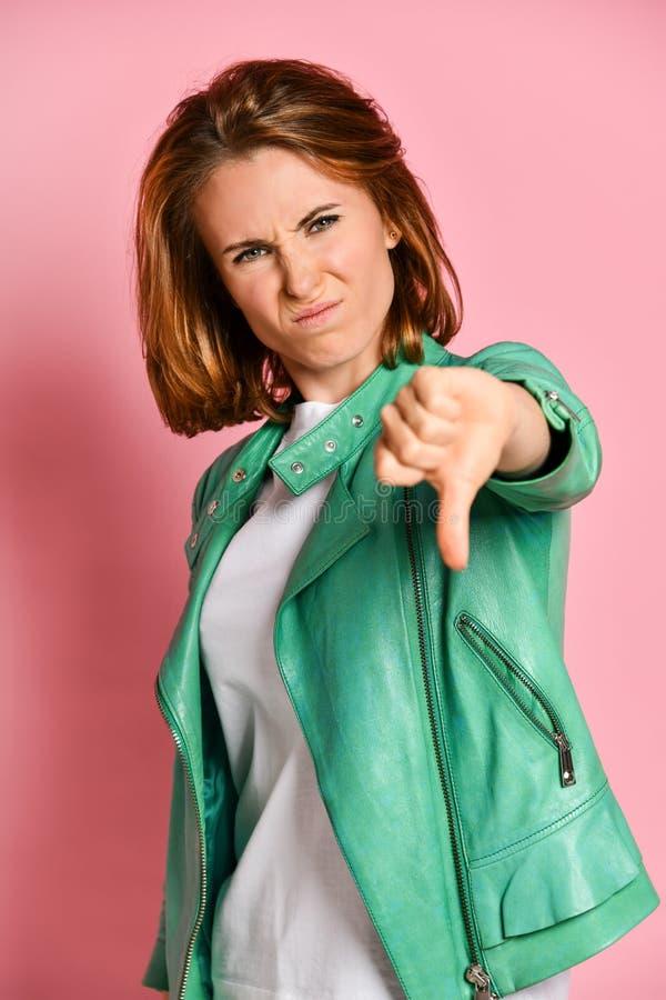 Retrato da mulher desagradada que está mostrando o polegar para baixo imagens de stock