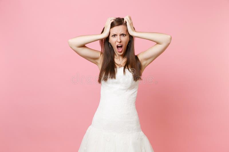 Retrato da mulher descontentada irritada da noiva em aderir-se gritando estando branco do vestido de casamento a dirigir isolado  fotografia de stock