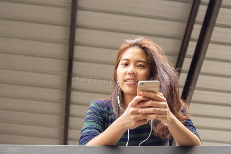 Retrato da mulher do adolescente do asiático 20s para escutar a música com fone de ouvido fotos de stock royalty free