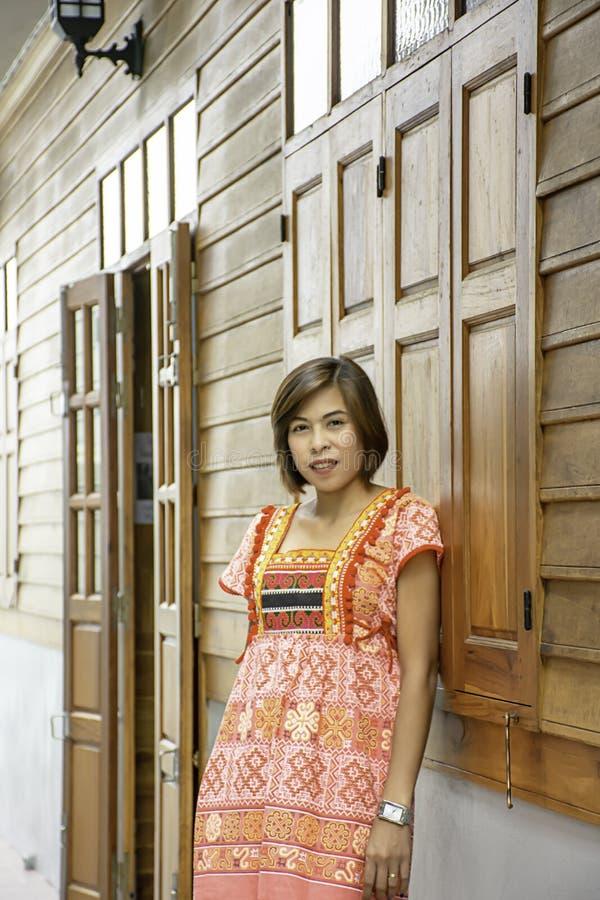 Retrato da mulher do Asean que veste um nativo da parede de madeira do fundo do norte de Tailândia fotografia de stock