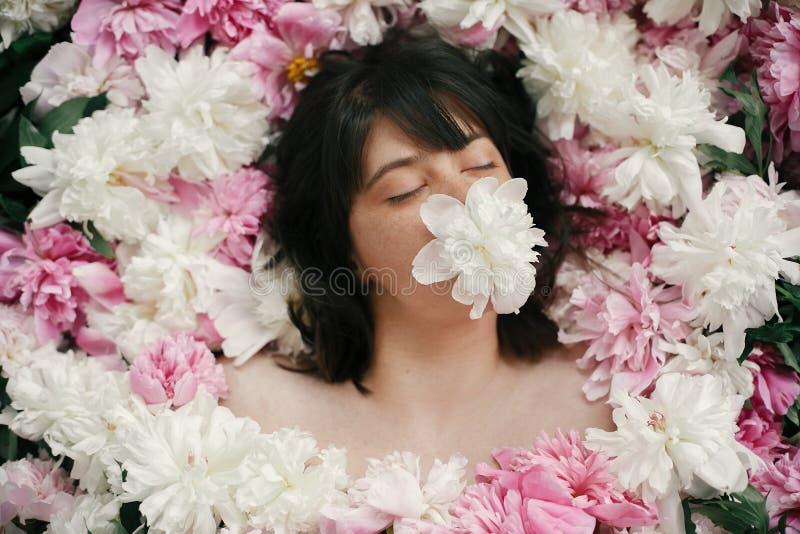 Retrato da mulher do boho com a peônia branca na boca que encontra-se em peônias cor-de-rosa Foto floral da arte criativa Conceit fotos de stock royalty free