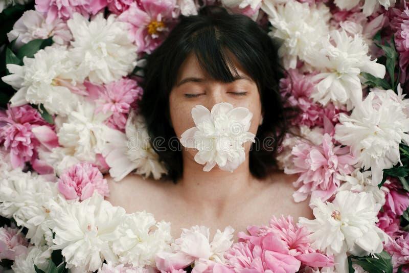 Retrato da mulher do boho com a peônia branca na boca que encontra-se em peônias cor-de-rosa Foto floral da arte criativa Conceit fotografia de stock royalty free