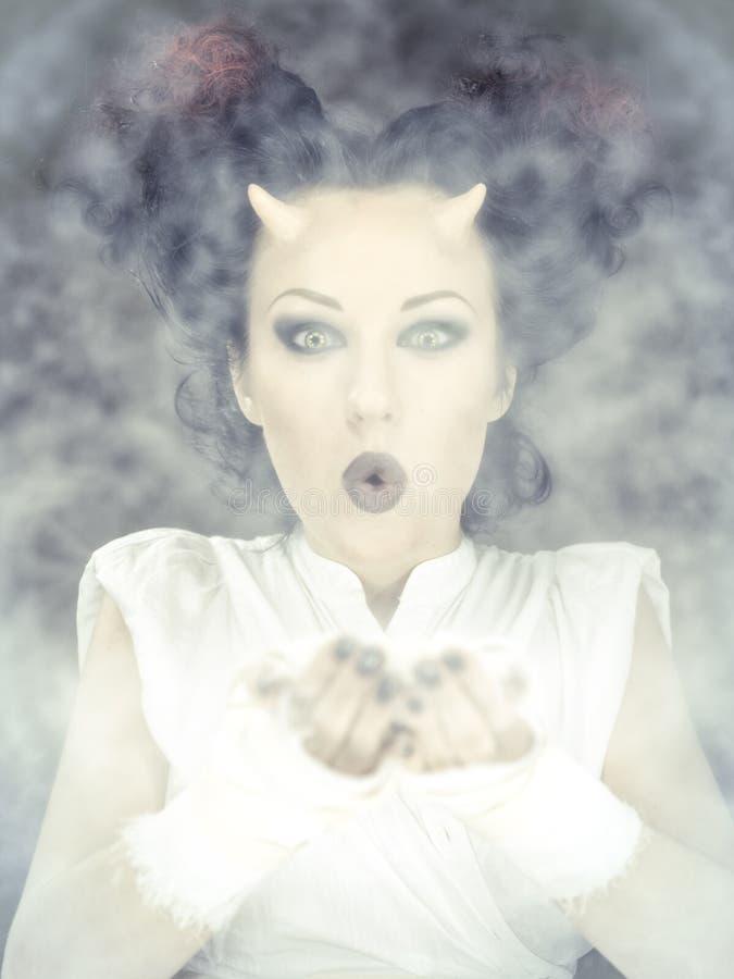 Retrato da mulher do diabo que funde um pó branco fotografia de stock