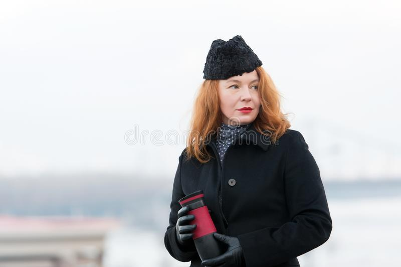 Retrato da mulher do gengibre no revestimento e no chapéu pretos com bordos vermelhos Retrato da mulher que guarda a garrafa térm imagem de stock royalty free